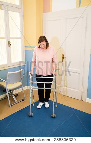 Woman Using Walker In Hospital After Surgery