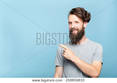 Smiling Young Hipster Man Pointing Sideways With Index Finger. Copy Space For Text Or Product Advert
