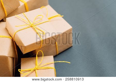 Assortment Of Presents Wrapped In Craft Paper Tied With A Yellow Twine. Holiday Gifts On Christmas O