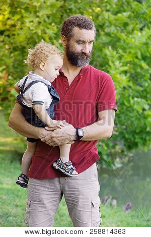 Father Holding His Son In The Park