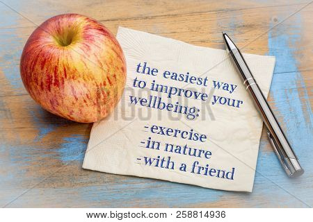 advice on improving your wellbeing - exervice, in nature, with a fiend - handwriting on napking with a fresh apple