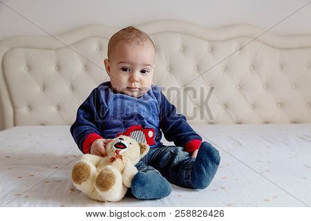 Baby Boy In A Blue Sweater Sitting On A White Bed With A Soft Toy Bear.
