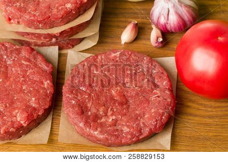 Various Raw Burger Ingredients On Wooden Desk