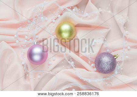 Beautiful Christmas Composition With Christmas Balls On A Pink Folded Silk. Flat Lay Composition For