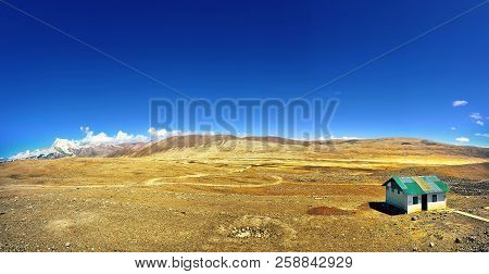 a house on a deserted land with arid soil and blue sky poster