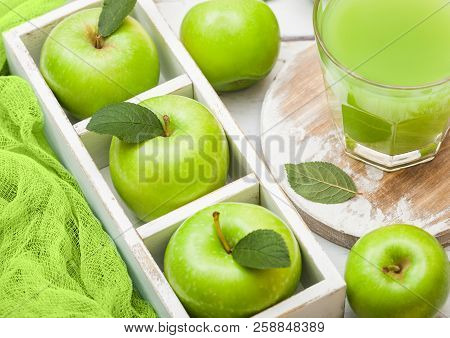 Glass of fresh organic apple juice with granny smith green apples in box on wood background. poster