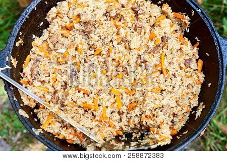 Top View Of Stirring Central Asian Dish Plov In Kazan Pot On Oven