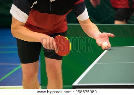 Table tennis player serving, focus at the ball