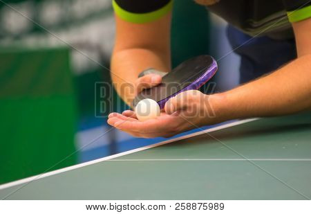 Table tennis player serving, close up