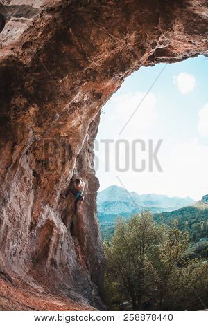 A Woman Climbs The Rock. Rock In The Form Of An Arch. Cave. Extreme Sports. The Athlete Trains On A