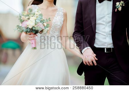 Close-up Photo Of Married Couple Walk Together Outdoors, Wedding Day. Bride Ant Groom Holding Hands