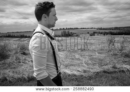Man Wearing Tuxedo Walks Through Field In Countryside