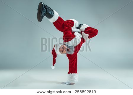 Funny Serious Guy With Christmas Hat Dancing At Studio. New Year Holiday. Christmas, X-mas, Winter,