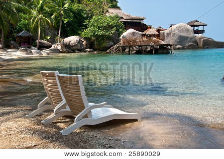 Chairs on tropical beach - abstract vacation background