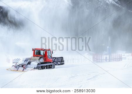 Modern Tracked Machine For Grooming Snow, Going Into A Snow Blizzard Made By Snow Cannon, In The Alp