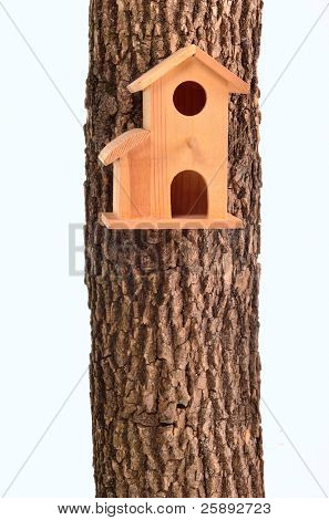 Modern starling-house on a tree trunk isolated on white background