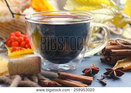 A Cup Of Mulled Wine Surrounded By Yellow Autumn Leaves And Spices, Cinnamon Sticks, Anise, Cloves.