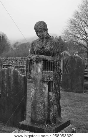 Black And White Photo Of A Cemetery Gravestone Monument Depicting A Lady Leaning On A Cross And Look