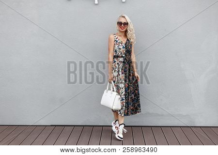 Beautiful Young Woman Model With Sunglasses With Stylish White Bag And Fashionable Dress With Patter