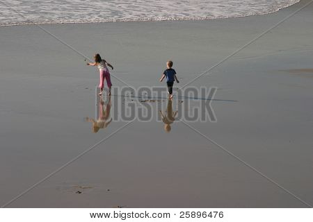 Two unidentifiable children play on the wet sand with excelent reflections and shadows on the beach