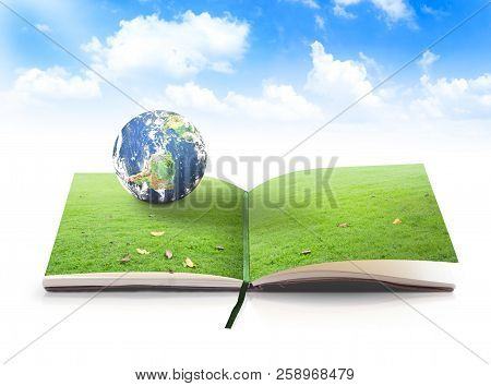 World Environment Day Concept: Earth Globe Rest On Green Grass Of Nature Book Over Blue Sky Backgrou