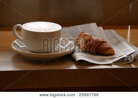 Seattles favorite drink Coffee with the morning paper and a croissant