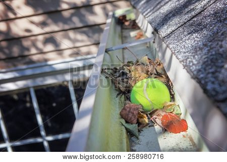 poster of Tennis ball stuck in gutter on a roof