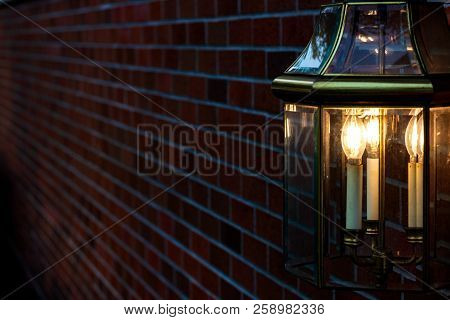 Lamp Mounted On A Brick Wall Illuminating Golden Light In The Darkness