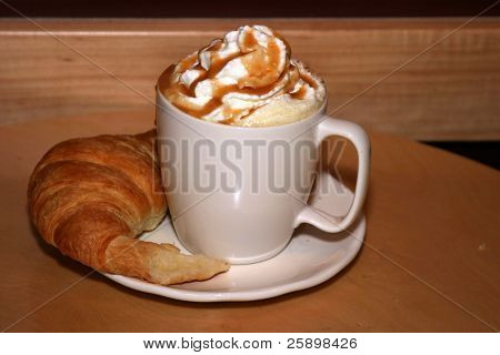 Latte with croisant and whipped cream and chocolate power