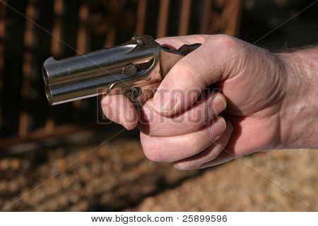 an antique 2 shot .45 cal derringer hand gun easly fits in the palm of a mans hand
