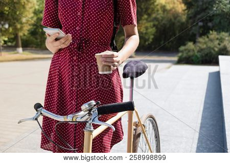 Woman In Polka Dot Dress With  Bike Commuting, Checking Mail Online And Having Coffee. Female Person