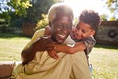 Senior black man sitting on grass, embraced by his grandson poster