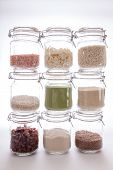 Food ingredients. Glass kitchen storage jars with various cooking foodstuff including himalayan pink mineral salt, dried coconut, arborio rice, long-grain rice, organic wheat grass and natural sugar. poster