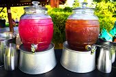 Jugs of cold huckleberry lemonade and iced tea on galvanized aluminum tubs displayed at an outdoor event poster