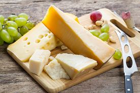 Set Of Various Cheese With Grapes And Knife On Wooden Table