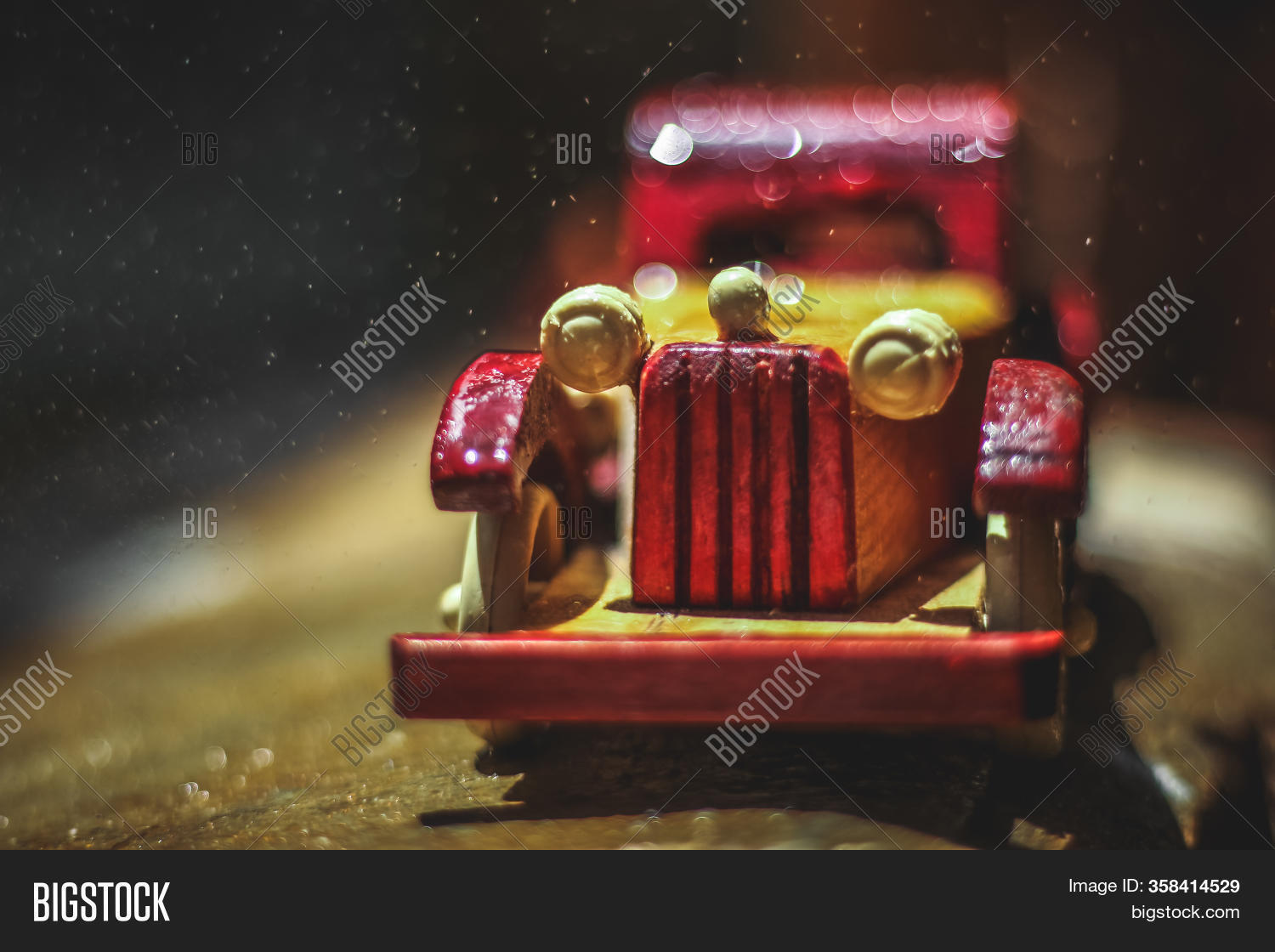 Vintage Toy Car Under The Rain On The Road. Miniature Car Toy In Rain. Red And Yellow Vintage Car On