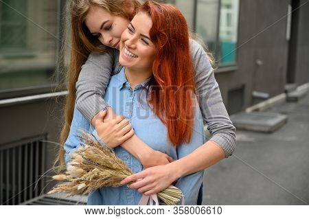 Same-sex Relationships. Happy Lesbian Couple With Dried Flowers. The Girl Gently Hugs The Red-haired