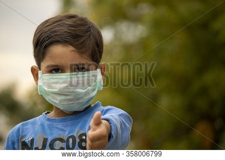 Indian Child With Mask Showing Thumbs Up During Corona Virus Lockdown Days In India