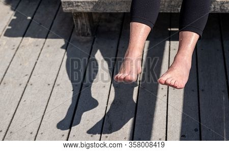Senior Woman Is Holding Her Wet Feet Up In Sun To Dry Off, Evaporate Water