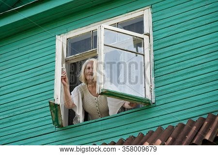 Woman Grandmother Standing Near Window Looking Outdoor In Green Wooden House
