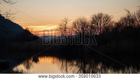 Sunrise, sunset on lake. Silhouette of trees reflected on the pond and colorful sunbeams colorize the water. Sky and mountains background. Wallpaper.