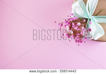 Gift Box With A Bouquet Of Spring Flowers On The Pink Table Top