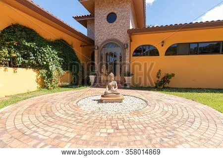 Orosi Costa Rica March 17 Buddha Statue In Front Of The Main Entrance Of A Luxury Colorful Residence