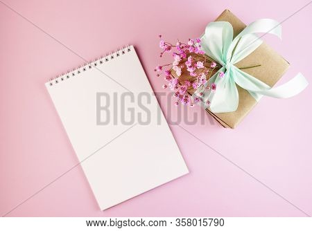 Gift Box With A Bouquet Of Spring Flowers On The Pink Table Top. A Box Of Paper With A Blue Bow On A