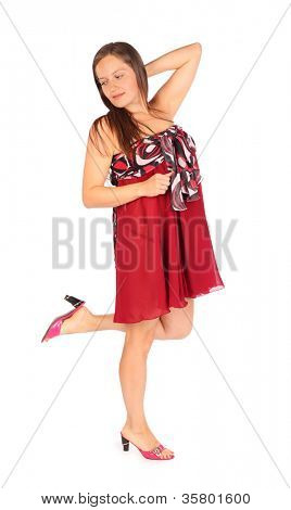 Beautiful dreaming woman dressed in red pareo poses in studio on white background.