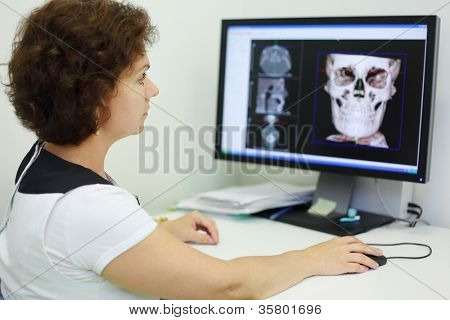 Dentist carefully looks jaw and skull X-rays at computer monitor in dental clinic.