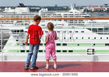 Boy and his younger sister stand with pieces of bread for seagulls in hands on deck of ship.