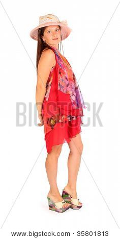 Fine woman dressed in bright pareo and hat poses in studio on white background.
