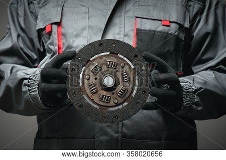 A Car Mechanic Is Showing An Old Car Clutch Disk Close Up.