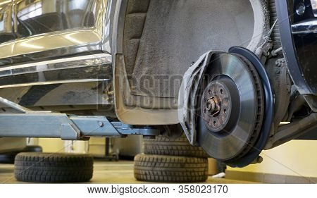 Modern Luxury Car In Service Raised On A Lift. Brake Disc, Brake Caliper Mounted On A Modern Car. Co